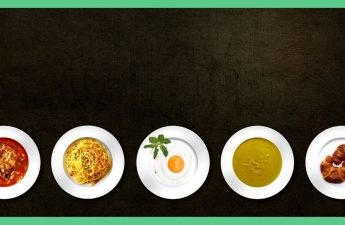 The image shows a dark brown surface with five plates lined up next to one another. The plates all have different food items on them.