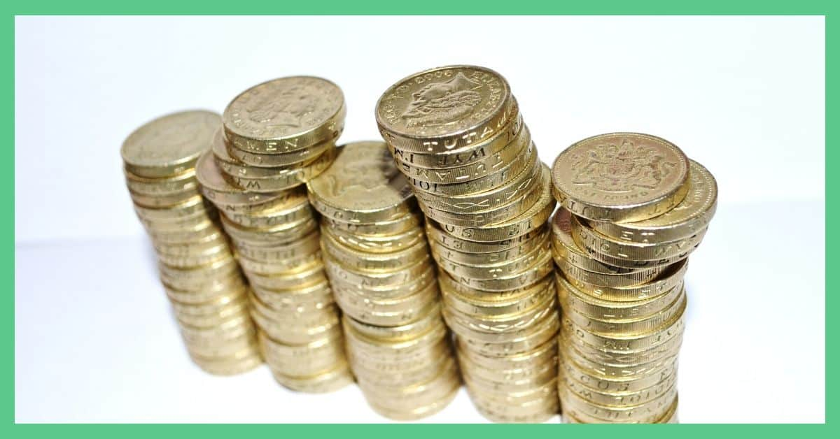 The image shows stacks of pound coins (GBP) linked up next to one another against a white backdrop.