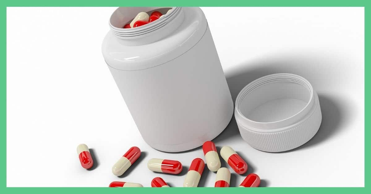 A white pill tub. The lid is off. You can see white and red capsules within the medicine tub and around it.