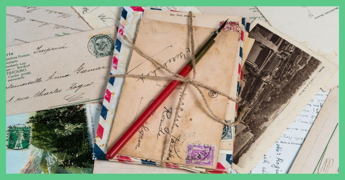 A pile of postcards and letters. The postcards are batched together with twine tied around them.