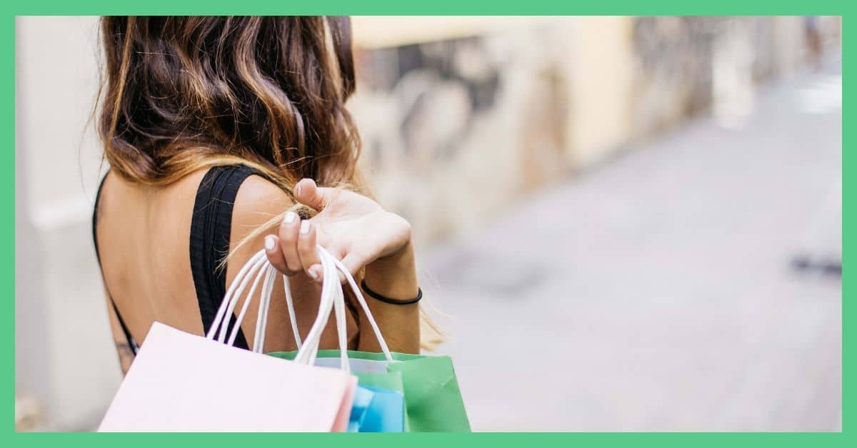 The image shows the back of a woman. She is holding paper shopping bags.