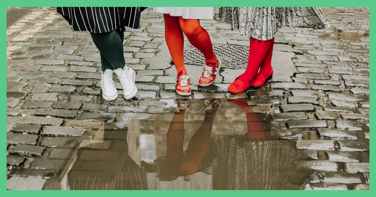 Three pairs of legs stood on a cobbled street. They are all wearing Snag Tights. The first person is wearing green-coloured tights, the second person is wearing burnt-orange-coloured tights and the third is wearing deep-red-coloured tights. You can see a puddle in front of the three people and you can see part of their reflection within the puddle.