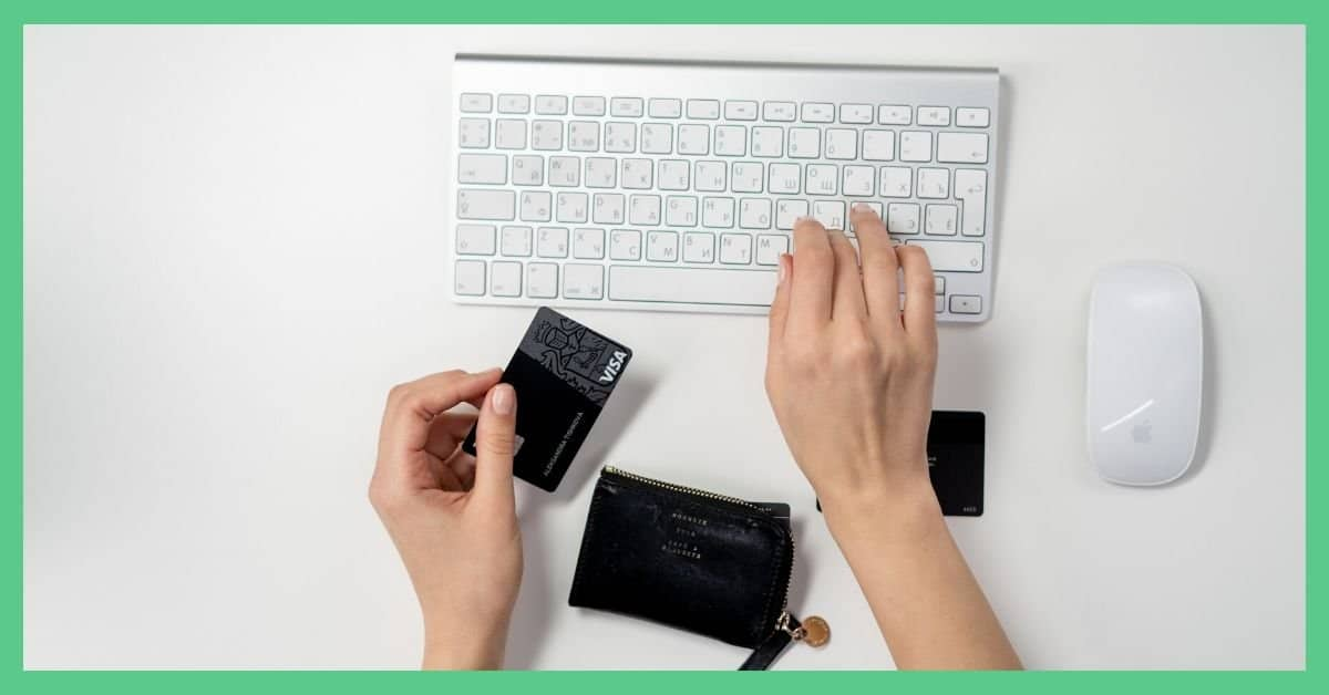 Two hands over a white keyboard. In the left hand, the person is holding a black credit card.