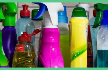 The image shows lots of cleaning bottles lined up next to one another. There is a pink bottle, a yellow bottle, an orange bottle, a green bottle, a purple bottle and a green bottle. The image has a green border around it.