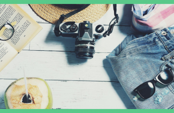 The image shows some travel items laid out. Including a camera, a straw hat, a book, some shorts and an open coconut. The background is white and the image has a green border. The image is being used as a feature image on an article about armchair travel.