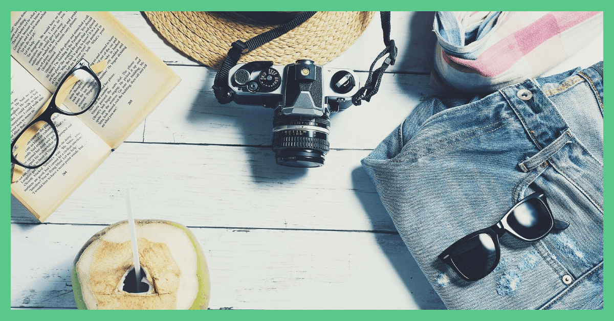 Travel items laid out. Including a camera, a straw hat, a book, some shorts and an open coconut.