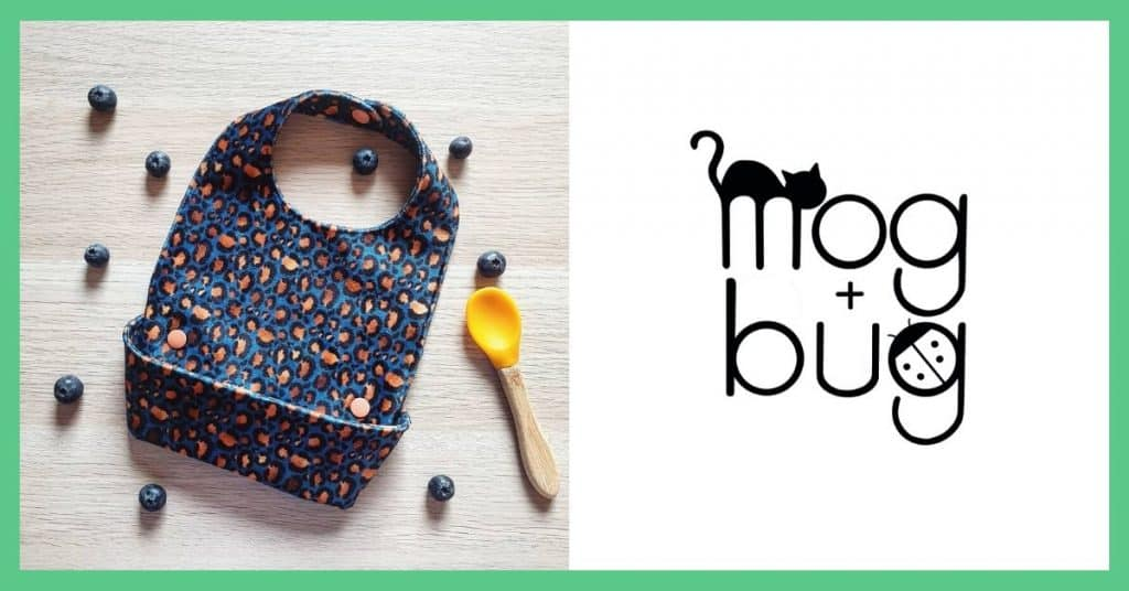 The image shows a cloth bib on a wooden surface with a yellow spoon and some blueberries around it. Next to it you can see the mog and bug children's wear logo which is black on a white background. The images are side by side and they both has a green boarder around them.