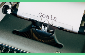 The image shows a typewriter. The paper in the typewriter has the word 'goals' typed out. The image has a green border.