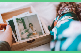 The image shows somebody looking at some photographs in a wooden box. The image has a green border.