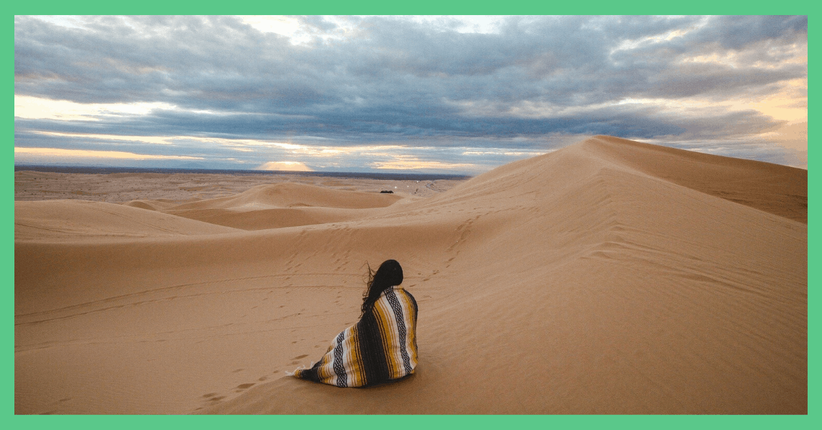 A woman sat alone on a sand dune.