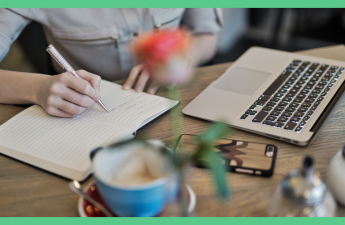 The image shows a woman sat on a desk, writing in a notepad. There's also a cup of coffee and a laptop on the table. The image has a green border. and it's being used as a feature image in an article about how to get paid to write.