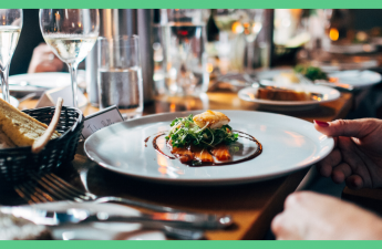 The shows a plate of food, surrounded by wine glasses, on a table to a restaurant. The image has a green border.