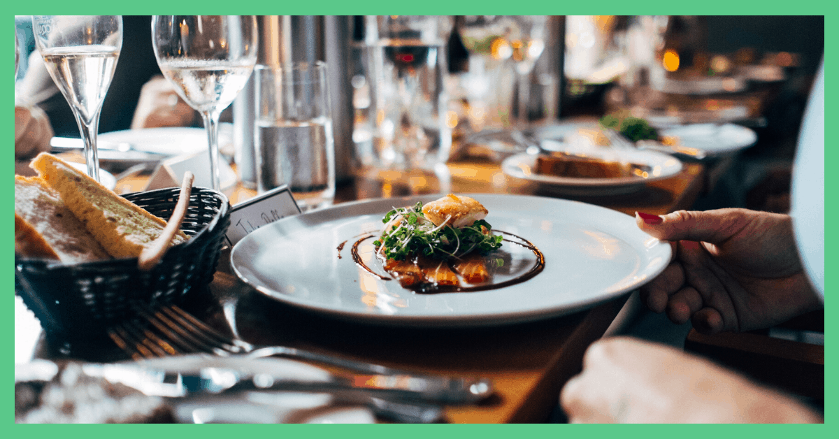 A plate of food, surrounded by wine glasses, on a table to a restaurant.