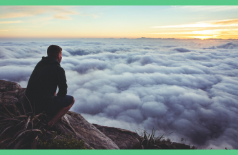 The image shows a silhouette of a man, sat on a rock, looking out at clouds. The image has a green border.