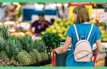 The image shows the back of a woman in a supermarket. She is in the fruit and vegetable aisle. She is wearing a blue t-shire and has a pink backpack on. The image has a green border.