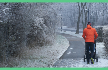 The image shows the back of a man in an orange jacket, pushing a baby in a pushchair. He is walking down an icy road. The image has a green border.