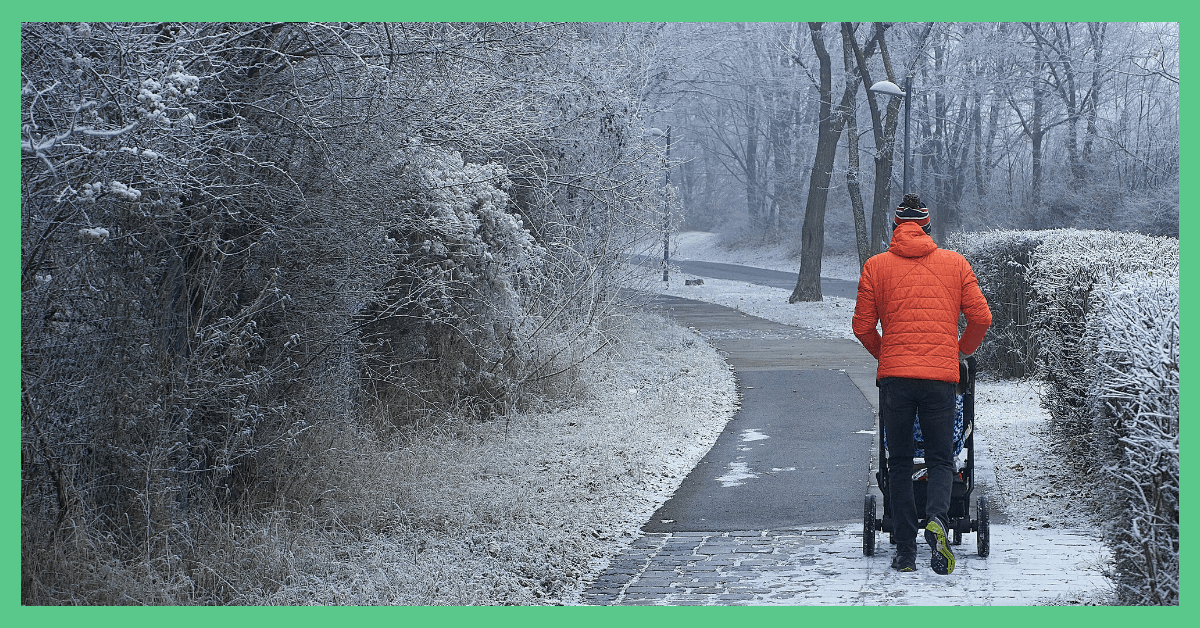 The back of a man in an orange jacket, pushing a baby in a pushchair. He is walking down an icy road.