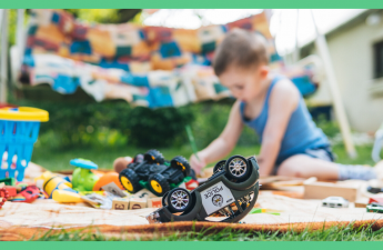 The image shows a little boy sitting playing with toy cars on a picnic blanket. The image has a green border.
