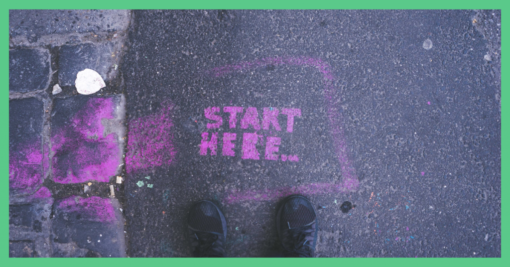 The image shows somebody standing on pavement. The pink paint on there says: 'start here'. The image has a green border.