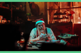 The image shows Father Christmas, sat in a dark room. He has cash in his hand and he's looking at it with a concerned look on his face. The image has a green border.