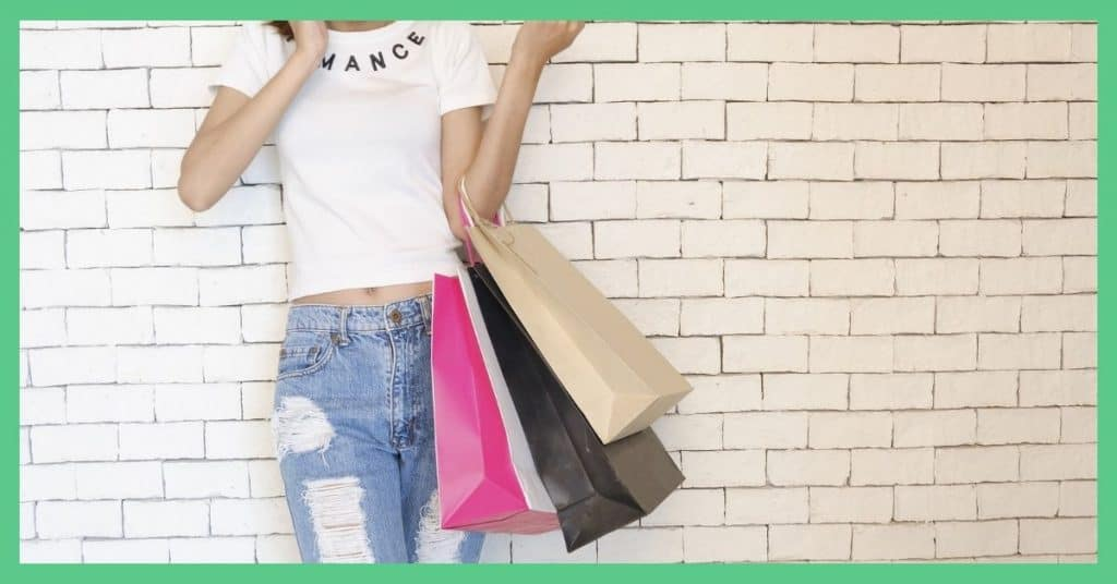 Loyalty cards, cashback, Shoppix - free money in the UK - from shopping. Image shows a woman holding shopping bags, stood by a wall.