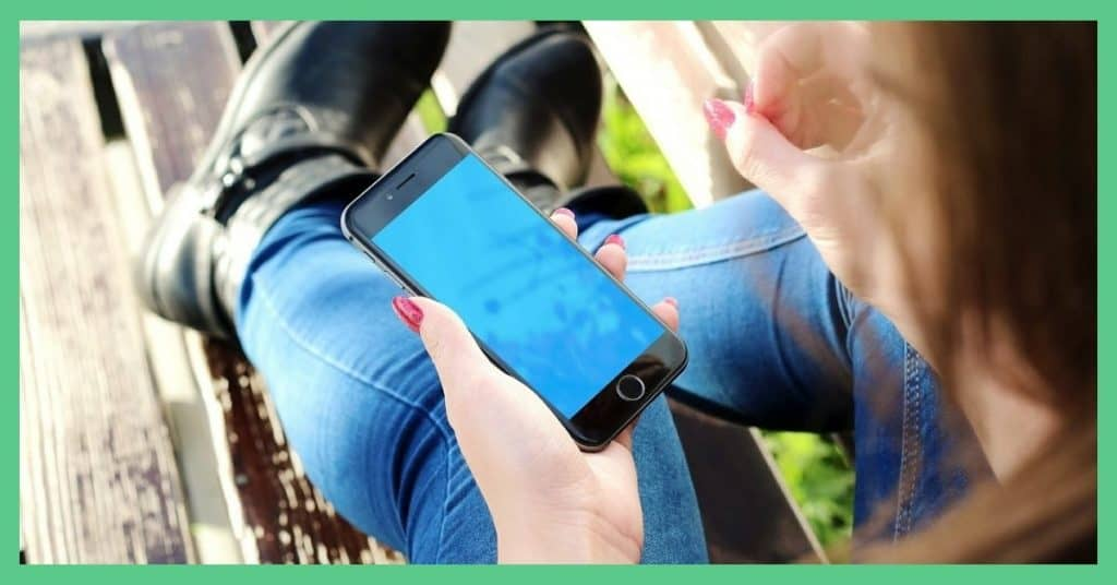 Pingit and Airtime Rewards - free money in the UK - from your phone. Image shows a woman looking at her smartphone.