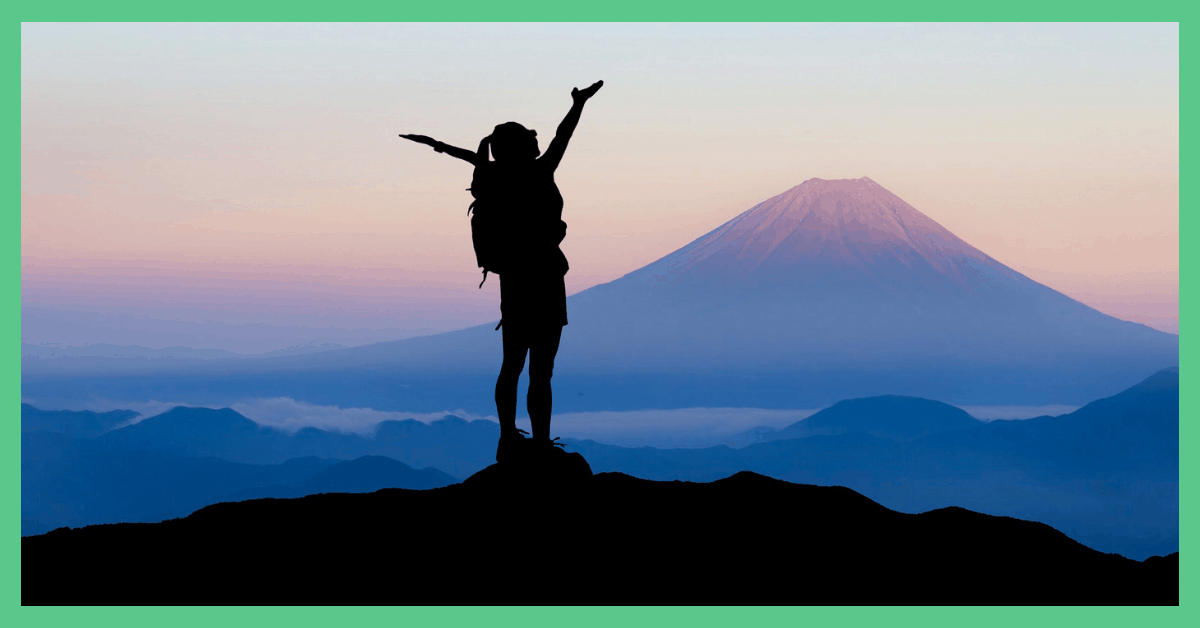 The image shows somebody celebrating on top of a mountain. The image has a green border.