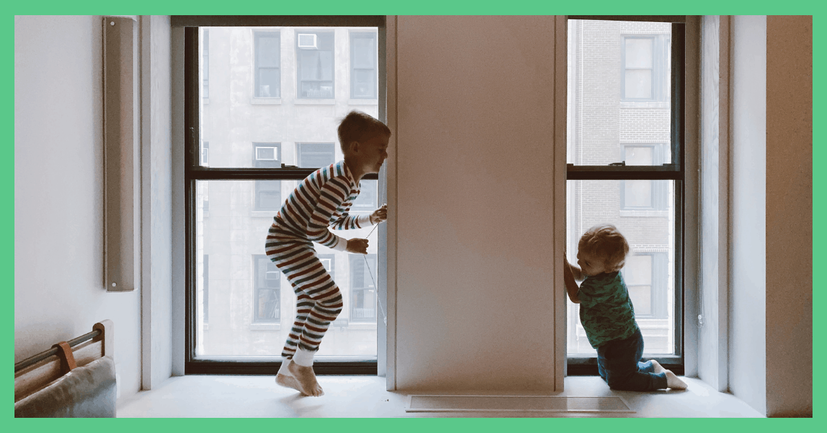 The image shows two children jumping up and down near a window.