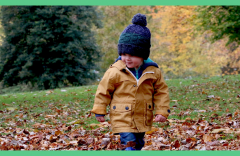 It image shows a toddler walking through leaves. He is wearing a blue wooly hat. The images has a green border. The image is being used in an article about things to do in Autumn with your toddler.