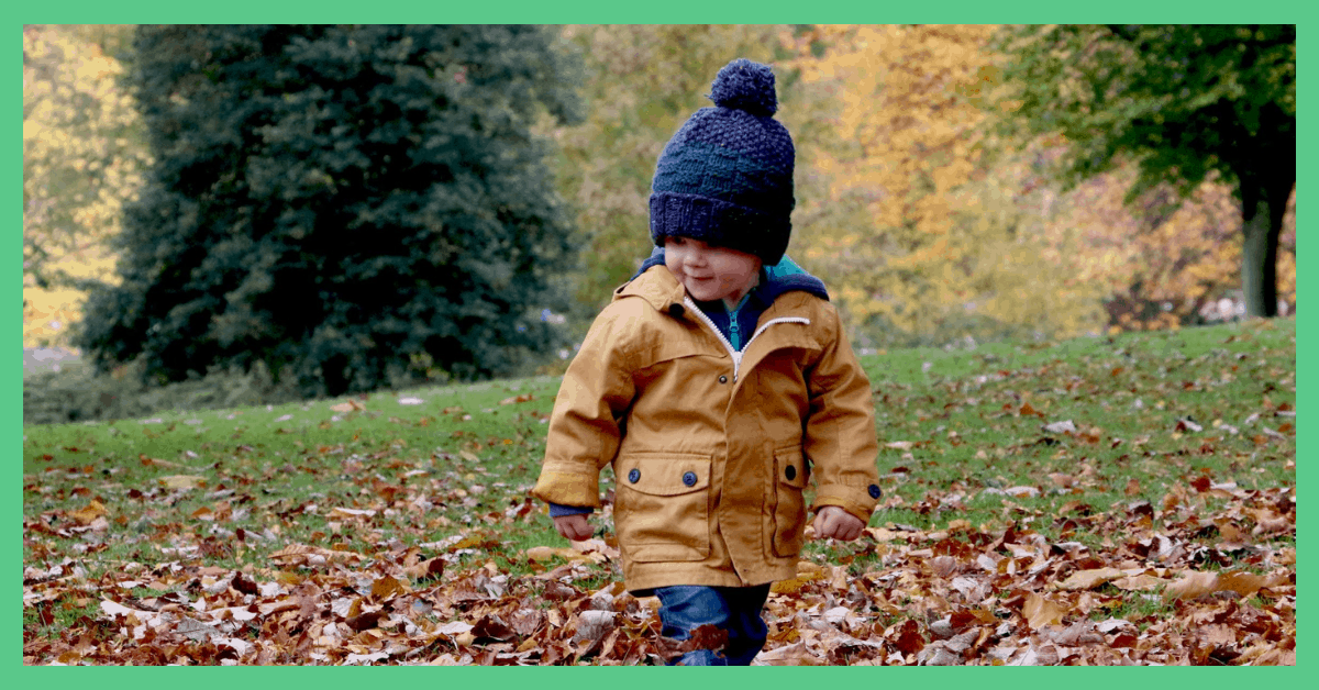 A toddler walking through leaves. He is wearing a blue woolly hat. This is being used in an article about things to do in Autumn with your toddler.