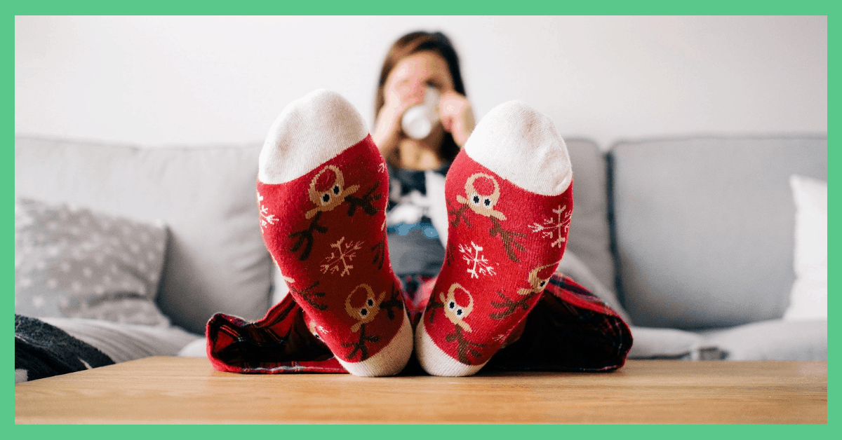There's a person with their feet up. They are sipping from a mug. Being used to illustrate the betwixmas period.