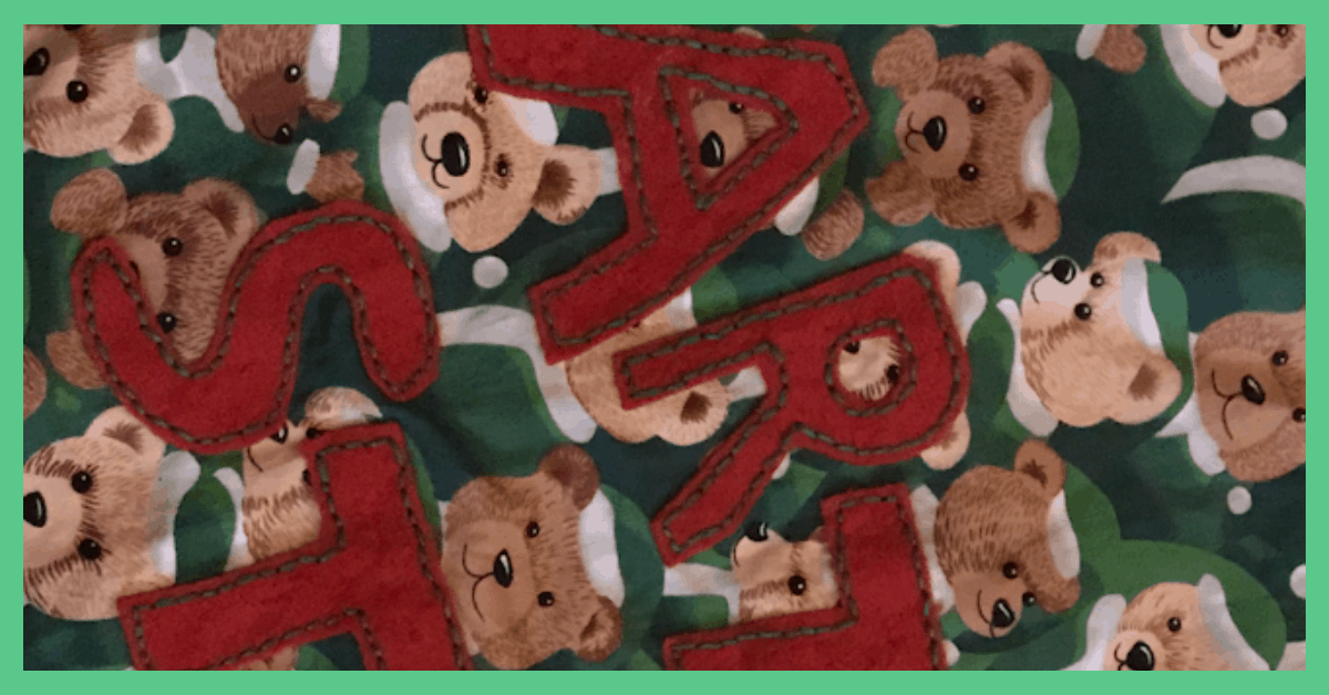 The image shows some bear fabric. The bears are wearing green festive clothing. The letters ART ST can be seen sewed onto the fabric. This fabric forms part of a personlised Christmas sack. The image has a green border.