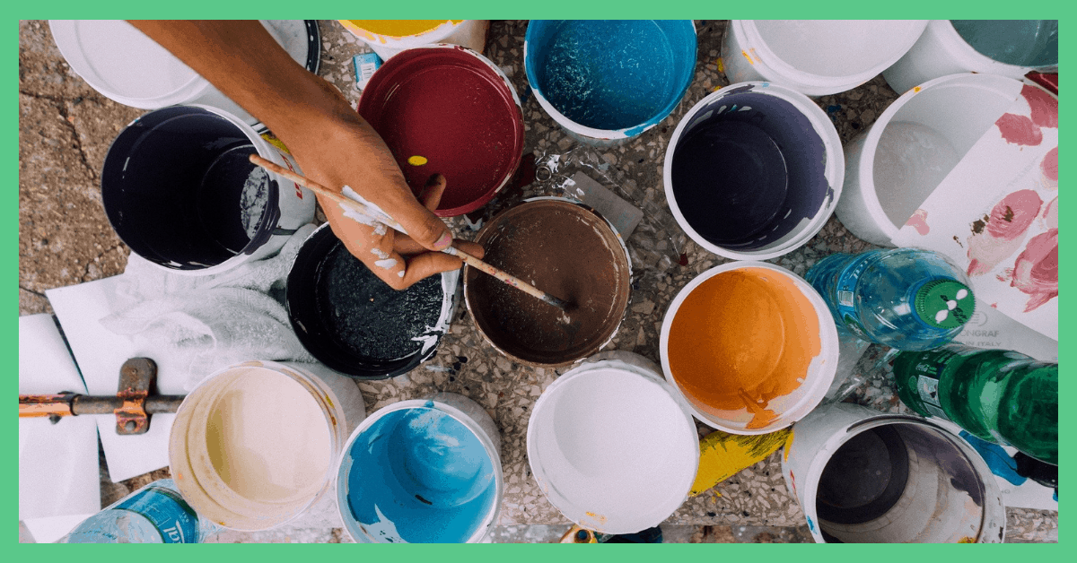 The image shows some open paints and somebody dipping a paint brush in one of them. The image has a green border.