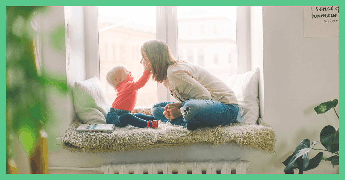 Image shows a mother and a son sat by a window. The picture has a green border.