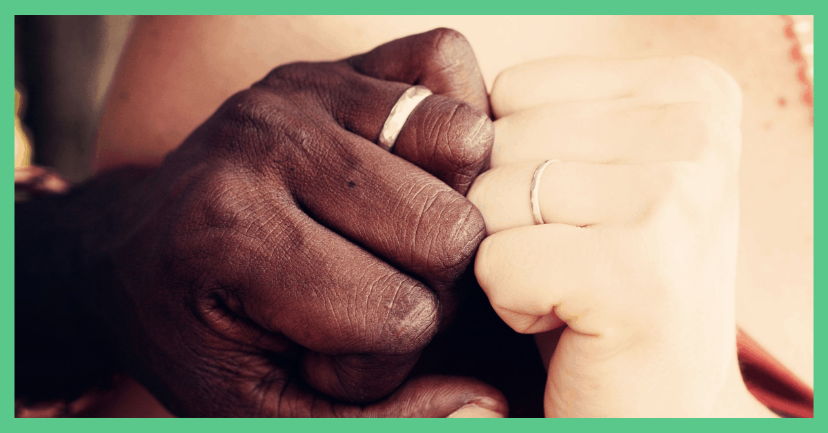 The image shows a couple holding hands, wearing wedding rings.